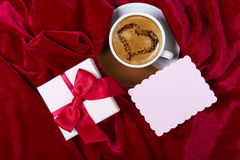 Cups with coffee, gift box and paper note. Romantic background. Cup with coffee with drawn heart on the foam, gift box and small paper note for text input on Stock Photos