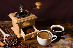 Cups of Coffee with Hand Grinder and Roasted Beans Royalty Free Stock Image