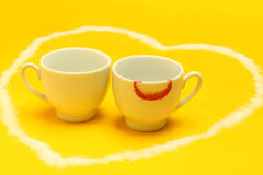 Cups of coffee inside a heart, one of them with lipstick Royalty Free Stock Images