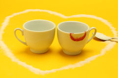Cups of coffee inside a heart, one of them with lipstick Stock Image