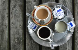 Cups of coffee, jug of milk, sugar on wooden table Royalty Free Stock Photos