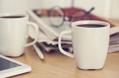 Cups of coffee and newspaper on table Stock Photos