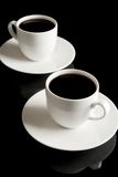 Cups of coffee with saucer isolated on black Royalty Free Stock Photo