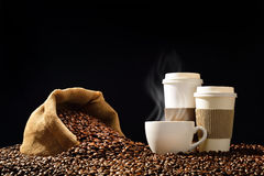 Cups of coffee. With smoke and coffee beans in burlap sack on black background Stock Photography