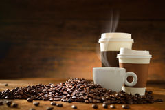 Cups of coffee. With smoke and coffee beans on old wooden background Stock Photography