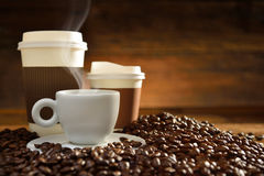 Cups of coffee. With smoke and coffee beans on old wooden background Royalty Free Stock Photography