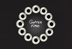 Cups with coffee, stacked in a circle. Clock consist of twenty cups. Black background. Concept time to coffee Royalty Free Stock Photography
