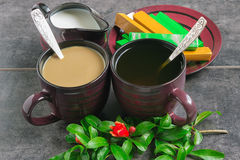 Cups of coffee and tea, chocolate, jug with milk and a branch with flowers Pomegranate Royalty Free Stock Photo