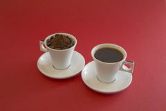 Cups of coffee. Two white cups of coffee on a red background, one filled with liquid coffee and the other one with ground coffee and beans stock photos
