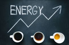 Cups of coffee under the trend line. Move up of energy. Trend up of energy. Arrow and graph. Coffee on a blackboard. Concept of en stock image