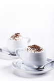 Cups of coffee with whipped cream and chocolate side view. Two cups of coffee with whipped cream and chocolate decoration on white background Stock Photos