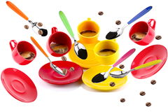 Cups of coffee. On white background in motion with flying spoons and coffee beans Royalty Free Stock Photos