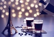 Cups of coffee witn Eiffel tower souvenir on a table and beautiful gold bokeh stock photos
