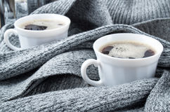 Cups of coffee wrapped in folds of gray woolen scarf Stock Photography
