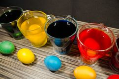 Cups with colored water and easter eggs royalty free stock image