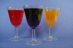 3 Cups of colorful cocktails mimosa and red wine set un on a blue background Royalty Free Stock Photos