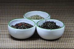 Cups containing herbs on a mat. Three white cups containing herbs on a mat background Royalty Free Stock Photos