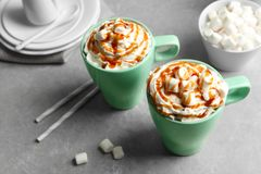 Cups with delicious caramel frappe on table Stock Image