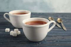 Cups of delicious tea with sugar. On table royalty free stock image