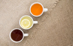 Cups with different types of tea. Cups with black, orange and lemon tea on the sackcloth Royalty Free Stock Images