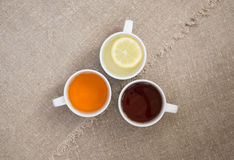 Cups with different types of tea. Cups with black, orange and lemon tea on the sackcloth Royalty Free Stock Photo