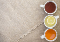 Cups with different types of tea. Cups with black, orange and lemon tea on the sackcloth Royalty Free Stock Photos