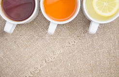 Cups with different types of tea. Cups with black, orange and lemon tea on the sackcloth Royalty Free Stock Image