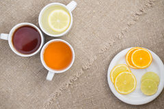 Cups with different types of tea. Cups different tea and plate with citrus on the sackcloth Royalty Free Stock Images