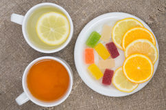 Cups with different types of tea. Cups different tea and plate with citrus on the sackcloth Royalty Free Stock Image