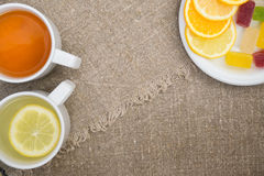 Cups with different types of tea. Cups different tea and plate with citrus on the sackcloth Stock Photo