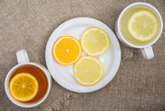 Cups with different types of tea. Cups different tea and plate with citrus on the sackcloth Stock Photography