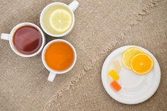 Cups with different types of tea. Cups different tea and plate with citrus on the sackcloth Stock Image