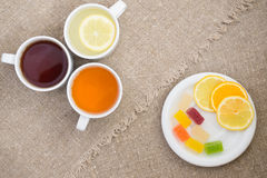 Cups with different types of tea. Cups different tea and plate with citrus on the sackcloth Stock Photos
