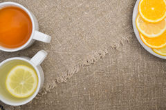 Cups with different types of tea. Cups different tea and plate with citrus on the sackcloth Stock Images