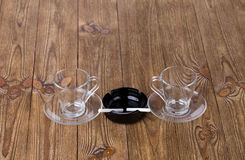 Cups with dish and cigarette in black ashtray Royalty Free Stock Photo