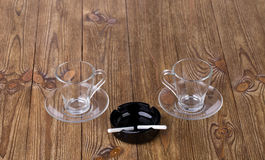 Cups with dish and cigarette in black ashtray Royalty Free Stock Photos