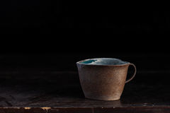 Cups and dusty on wooden. Old ceramic cups and dusty on a  wooden table Royalty Free Stock Image