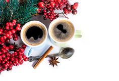 Cups of fragrant coffee on a Christmas background. Of fir branches, berries and cones Royalty Free Stock Photography
