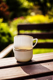 Cups in garden. Two white cups on the table in garden Stock Photos