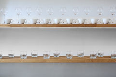 Cups and glasses on a shelf. Some cups and glasses on a shelf at wall Stock Photography