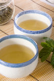 Cups with green tea. Two steaming cups of green tea on bamboo mat Royalty Free Stock Photos