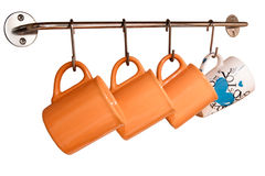 Cups hanging on the wall. Teacups orange hang on hooks on a white background Stock Images