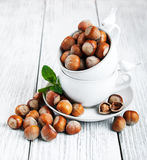Cups with hazelnuts. On a old wooden table Royalty Free Stock Image