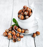 Cups with hazelnuts. On a old wooden table Royalty Free Stock Photo