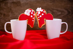 Cups with heart cookies for valentines day. Couple cups with heart cookies for valentines day Royalty Free Stock Photography