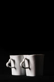 Cups with heart shape handle on black background Royalty Free Stock Photos