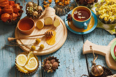 Cups with herb tea and pieces of lemon, dried herbs and different decorations stock photo