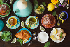 Cups of herbal tea with lemon and mint, ginger root and croissant on the wooden background, top view Stock Photography