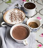 Cups of hot aromatic coffee and chocolate. Espresso, espresso macchiato and latte. On the background of the old table, antique tea royalty free stock photo