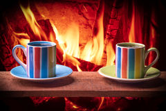 Cups of hot drink in front of warm fireplace. Holiday Christmas concept. Royalty Free Stock Photos